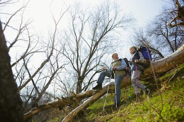 Persoonlijk praten. leeftijd familie paar man en vrouw in toeristische outfit wandelen op groen gazon in de buurt van bomen in zonnige dag. concept van toerisme, gezonde levensstijl, ontspanning en saamhorigheid.