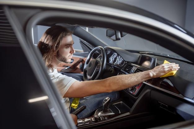 Persoonlijke auto. jonge, bebaarde nette man met spray en servet zittend op de bestuurdersstoel van auto afvegen dashboard