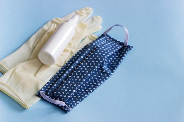 Persoonlijke beschermingsmiddelen masker, handschoenen en ontsmettingsmiddel op een blauwe achtergrond.