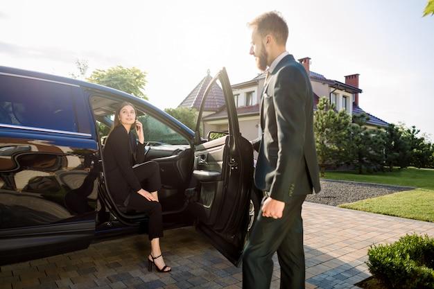 Persoonlijke chauffeur van de jonge man te wachten op zijn vrouwelijke baas, mooie jonge zakelijke dame in zwart pak, op parkeerplaats, haar te helpen uit de auto te komen