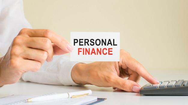 Persoonlijke financiën, bericht op visitekaartje getoond door vrouw die op rekenmachinetoets drukt op de werkplek in licht kantoor, selectieve focus, zakelijk en financieel concept