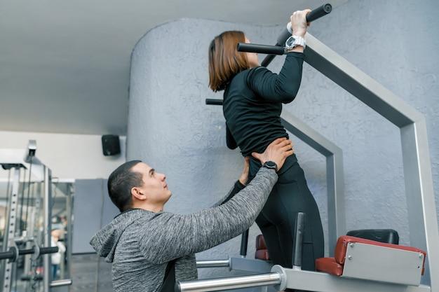 Persoonlijke fitness instructeur training jonge vrouw in sportschool.