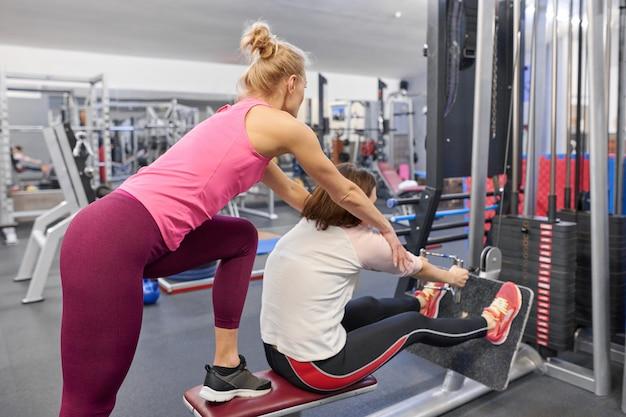 Persoonlijke fitnesstrainer werkoefening met volwassen vrouw in de sportschool