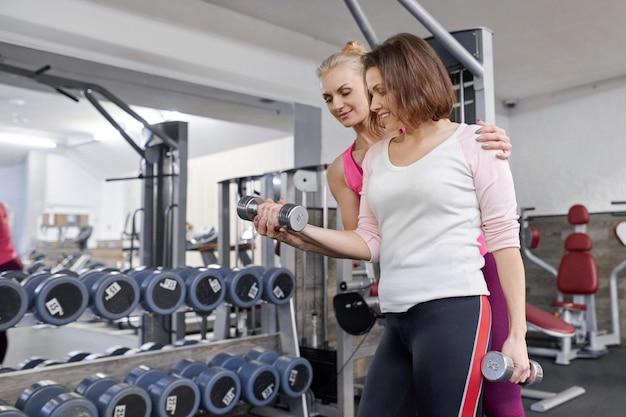 Persoonlijke gymnastiektrainer die rijpe vrouw bijstaan