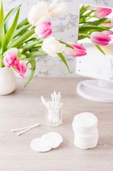 Persoonlijke hygiëne, netheid en huidverzorging. wattenschijfjes en wattenstaafjes in een glas op een tafel voor een spiegel en een boeket tulpen in een vaas. verticale weergave