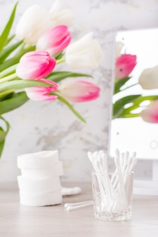 Persoonlijke hygiëne, netheid en huidverzorging. wattenschijfjes en wattenstaafjes op de tafel voor de spiegel. verticale weergave