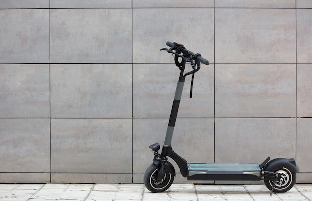 Persoonlijke mobiliteit voertuig elektrische scooter escooter geparkeerd in de stad met grijze muur achtergrond