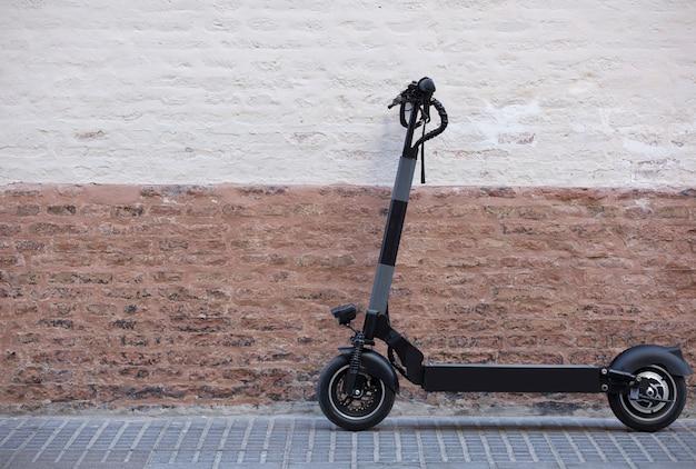 Persoonlijke mobiliteit voertuig elektrische scooter geparkeerd in de stad met rustieke bakstenen muur b