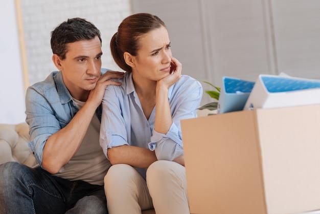 Persoonlijke problemen. emotionele ongelukkige jonge vrouw zittend op de bank en op zoek in de verte na het verliezen van haar baan terwijl haar vriendelijke attente liefhebbende echtgenoot haar knuffelde