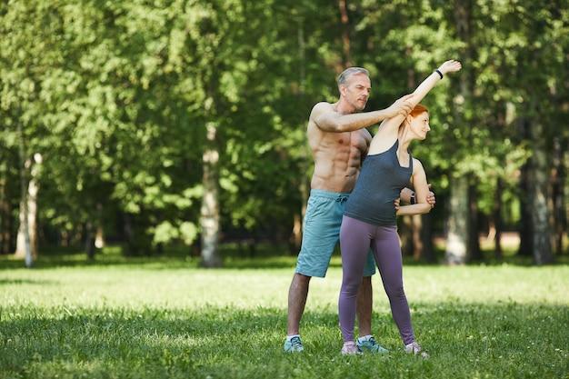Persoonlijke shirtless fitnessinstructeur die vrouw helpt om zijwaartse buiging in park te doen tijdens coronavirusbeperkingen