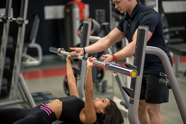 Persoonlijke trainer die de pers van de vrouwenbank in gymnastiek helpen