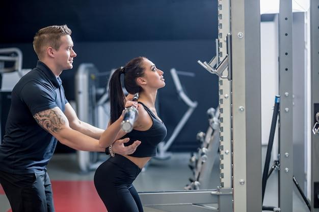 Persoonlijke trainer die een jonge vrouw helpt een barbell op te heffen terwijl het uitwerken in een gymnastiek