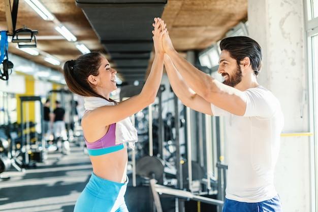 Persoonlijke trainer die high five geeft aan sportieve blanke vrouw met handdoek om haar nek. gym interieur.
