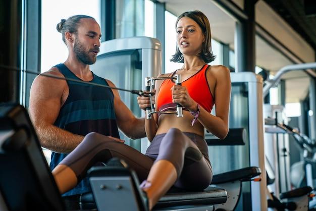 Persoonlijke trainer die vrouw helpt die in sportgymnastiek uitwerkt