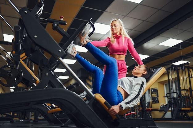 Persoonlijke trainer helpen vrouw in werkt op trainingsapparatuur binnen in fitnesscentrum sportieve levensstijl bodybuilding trainingsconcept