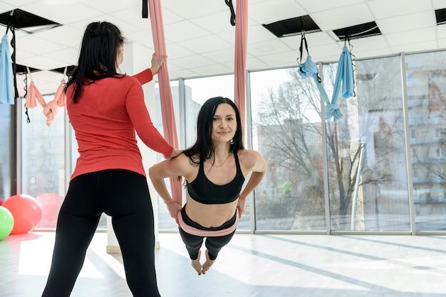 Persoonlijke trainer meewerkende vrouw warming-up voor fitness in de lichte sportschool. gezonde levensstijl