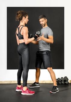 Persoonlijke training bijstaan van een vrouw met gewichten