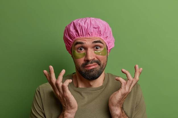 Persoonlijke verzorging, mannenhygiëne, schoonheidsroutineconcept. aarzelende ongeschoren europese man spreidt zijn handpalmen zijwaarts, draagt plekken onder de ogen, strijkt rimpels glad, draagt een badmuts, staat tegen een groene muur.