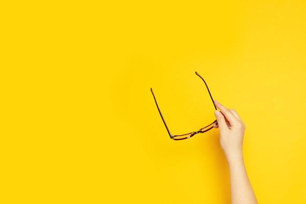 Persoonshand houdt een bril vast voor zicht op een gele achtergrond bovenaanzicht plat lag