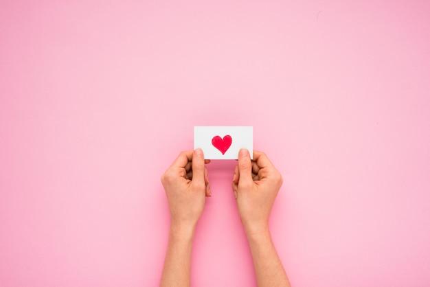 Persoonshanden die document met hartsymbool houden