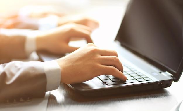 Persoonsteam typen op een moderne laptop op kantoor