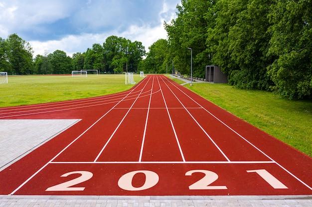 Perspectief aanzicht van een openluchtstadion met rode renbanen, met nummer 2021, nieuwjaarsvieringsconcept