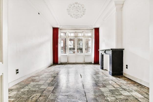 Perspectief aanzicht van lege klassieke stijl kamer interieur met wit stucwerk elementen en betegelde vloer met groot raam en open haard