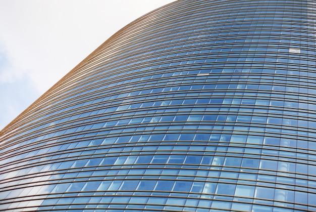 Perspectief en onderkanthoekmening aan geweven achtergrond van moderne glas de bouwwolkenkrabbers over blauwe bewolkte hemel