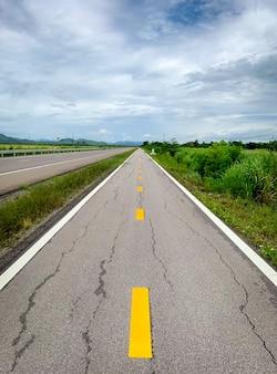 Perspectief gebarsten asfaltweg vooruit naar de berg