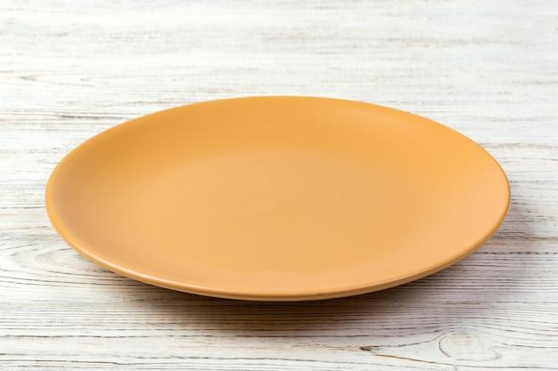 Perspectief. lege oranje steenschotel voor diner op witte houten