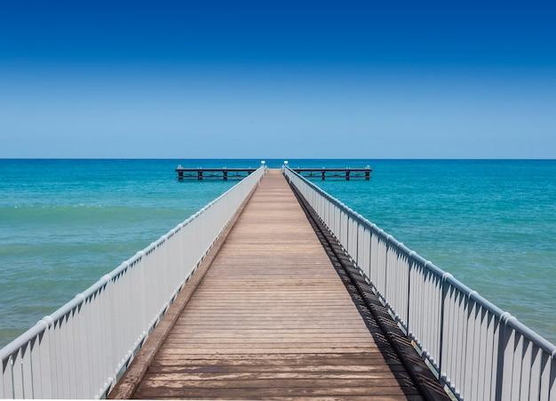 Perspectief uitzicht op een houten pier aan de kust met helderblauwe zee