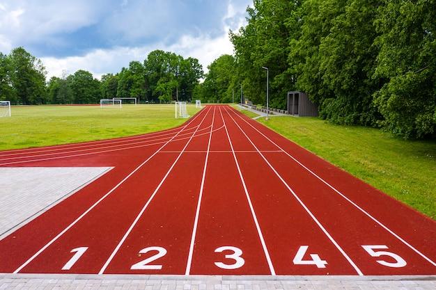 Perspectief van een openluchtstadion met rood genummerde atletiekbanen, infrastructuur voor sportactiviteiten