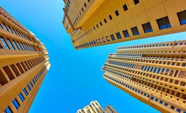 Perspectief van moderne flatgebouwen met meerdere verdiepingen tegen de blauwe hemel