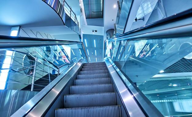 Perspectief van omhoog roltrap bij luchthaventerminal. afgezwakt in blauw