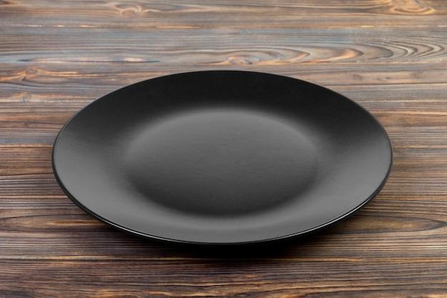 Perspectiefmening, lege donkere steenschotel voor diner op houten