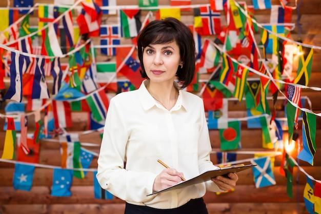 Perssecretaris van de vrouw op de internationale bijeenkomst tegen de achtergrond van de vlag.