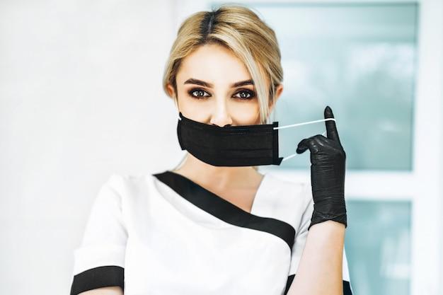 Pertrait foto van de vrouwelijke arts in zwart masker en zwarte handschoenen.