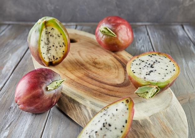 Peruaanse appelcactusvruchten heel en gesneden op houten standaard op grijs bord. wetenschappelijke naam cereus repandus