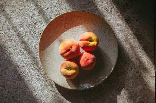 Perzik in een plaat bovenaanzicht op een getextureerde tafel