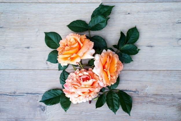 Perzik nam bloemenregeling toe die op houten grijze achtergrond wordt geïsoleerd