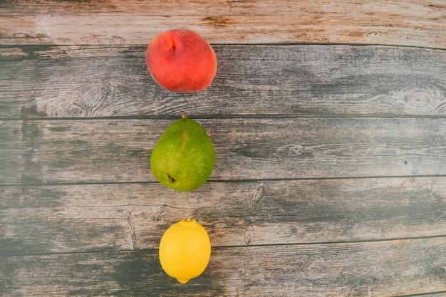 Perzik, peer, citroen op een houten achtergrond. houten blokken met de woorden vitamine c, vers fruit op de achtergrond, gezonde voeding of dieet concept. uitzicht van boven. plaats om te schrijven.