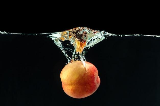 Perzik viel in het water met bubbels