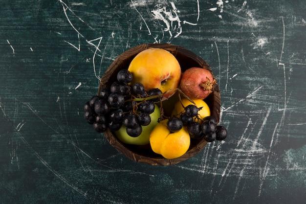 Perziken en druiven in een houten kom op zwarte bord in het midden