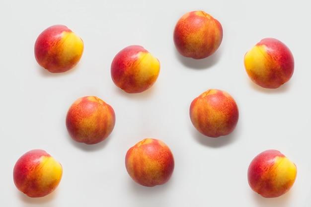Perziken geïsoleerd op een witte muur zijn gerangschikt in een patroon. fruitconcept, muren voor fruitwinkels of perzikolie, tekeningen voor tafelkleden en fruitdouchegels.