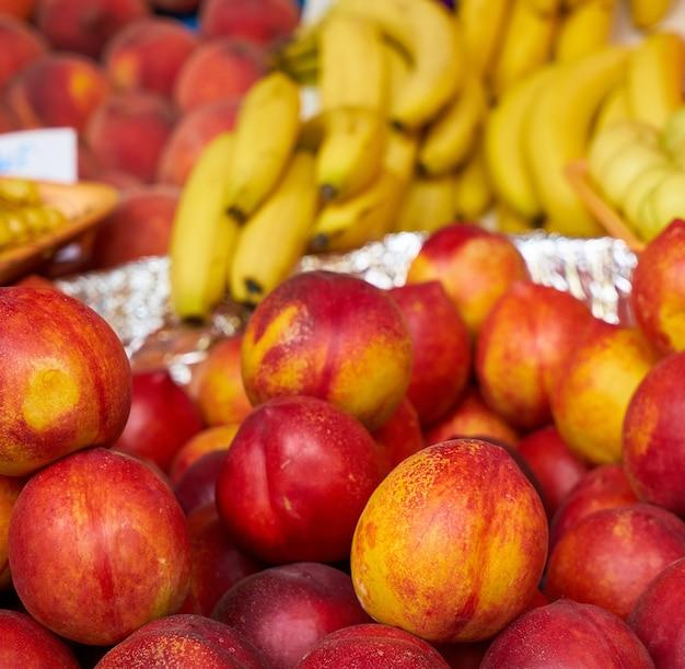 Perziken met bananen op de achtergrond