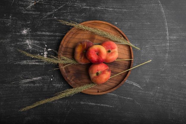 Perziken met groene kruiden in een houten schotel