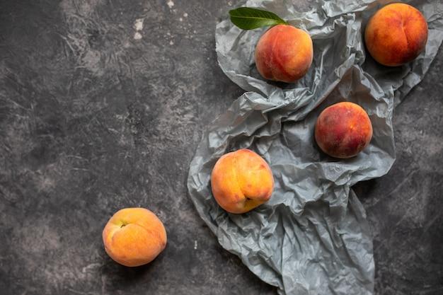 Perziken of nectarines in een grijze donkere stenen plaat met bladeren, bovenaanzicht