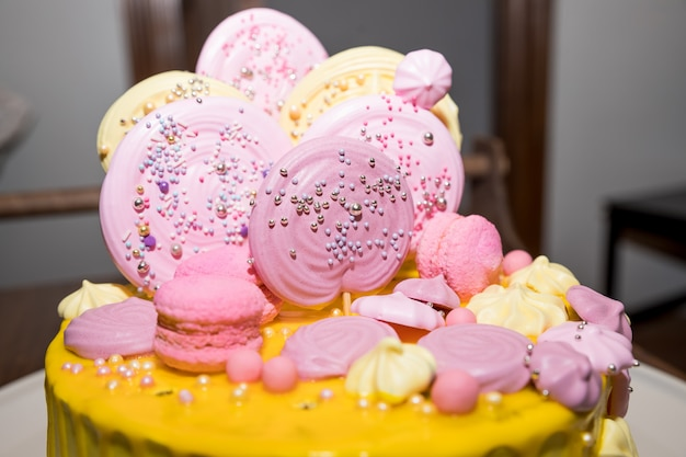 Perzikkleurige cake met meringue en snoep voor de verjaardag van een kind. vakantietafel voor kinderen, cake, snoep, zoet eten. candy bar.