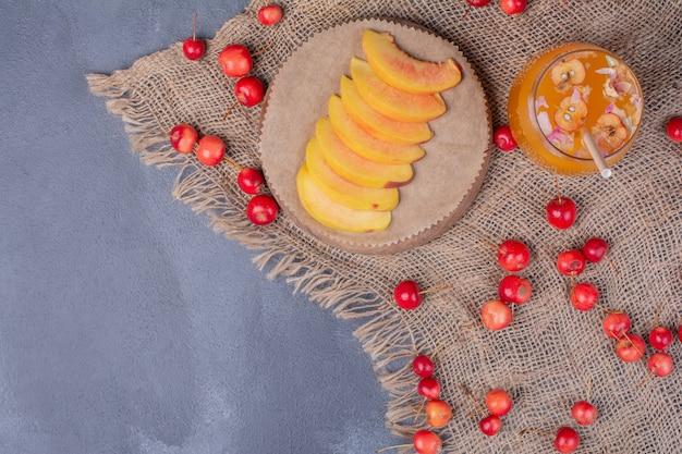 Perzikplakken, kersen en glas vruchtensap op blauw.