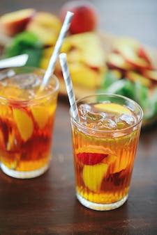 Perziksap in kopjes met plakjes fruit erin